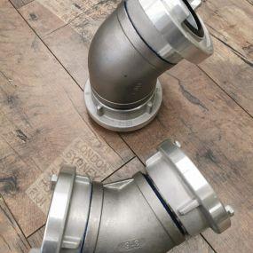 Edelstahlrohrbögen für Mast Tauchpumpen. Im Bild zusehen: ein Rohrbogen Storz B 45° mit 80mm Innendurchmesser, einer Festkupplung mit Verriegelungsrippen und einem drehbarem Knaggenteil Storz B.